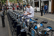 Two resturant chefs take a break by checking messages while resting on some Boris bikes in a narrow Soho street, central London.