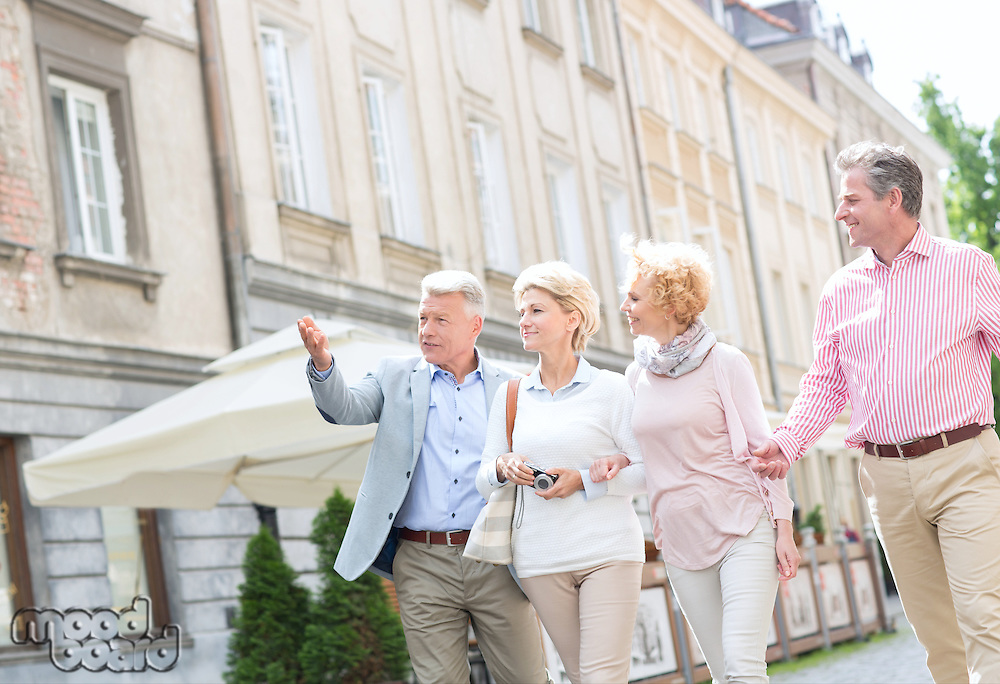 Man showing something to friends while walking in city