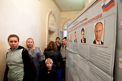 © licensed to London News Pictures. London, UK 04/03/2012. Russian citizens queuing to vote past a poster showing the candidates for the election for the President of the Russian Federation at the The Embassy of the Russian Federation in London today (04/03/2012) as the election for the President of the Russian Federation takes place. Photo credit: Tolga Akmen/LNP