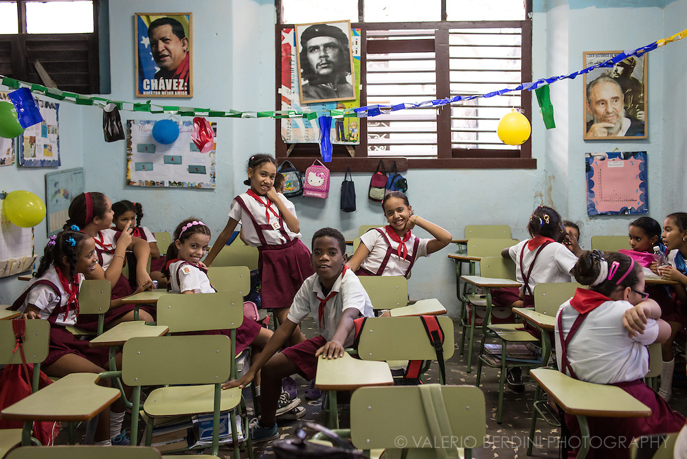 Children of a primary school class in Havana enjoy a break between lessons. On the wall pictures of Chavez, Che Guevara and Fidel Castro.