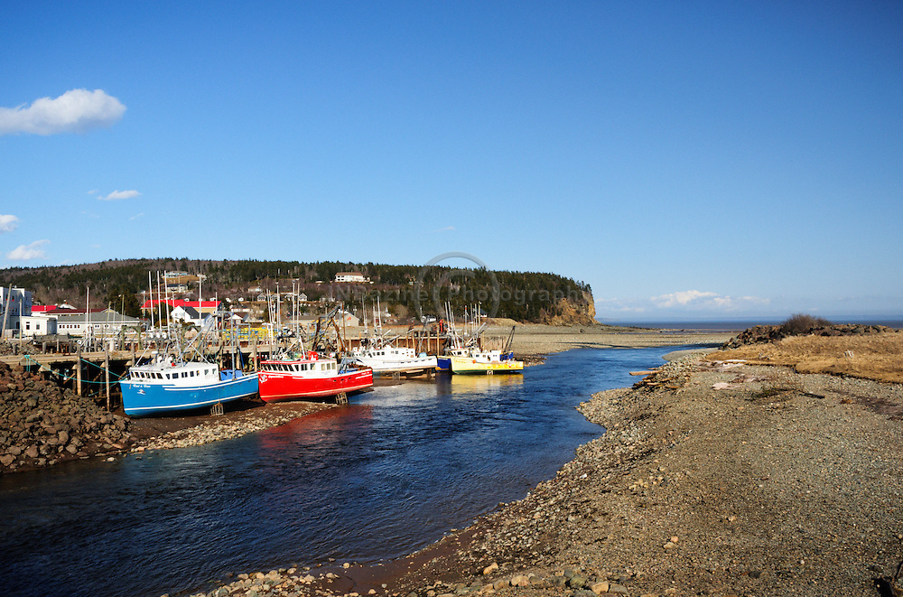 Crates hold fishing boats upright during low tide in Alma, NB Canada