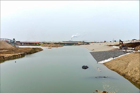 Nederland, Nijmegen, 26-11-2014 Aan de overkant van de Waal bij Lent wordt druk gewerkt aan het creeren van een nevengeul in de rivier om bij hoogwater een betere waterafvoer te hebben. Het is een omvangrijk project waarbij onder meer de pijlers van het spoorviaduct een bredere basis moeten krijgen omdat die straks in de loop van het water staan. Ook de n325 die vanaf de Waalbrug naar Arnhem loopt moet over 400 meter opnieuw worden aangelegd omdat het talud vervangen wordt door pijlers. De weg wordt via een bypass omgeleid. Het dorp veurlent komt op een kunstmatig eiland te liggen met twee bruggen als ontsluiting. Een voetgangersbrug en de andere voor normaal verkeer. Inmiddels begint de nieuwe kade aan de noordkant van deze geul vorm te krijgen. Ruimte voor de rivier, water, waal. In de nieuwe dijk wordt een drempel gebouwd die stapsgewijs water doorlaat en bij hoogwater overloopt. Measures taken by Nijmegen to give the river Waal, Rhine, more space to flow during highwater and to prevent the risk of flooding. Room for the river. Reducing the level, waterlevel. Foto: Flip Franssen/Hollandse Hoogte