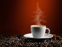 Christmas tree shaped steam rising over a cup of coffe latte standing on coffee beans isolated on dark red background