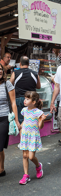 Little girl with parents making a classic hand gesture. Girl and parents enjoying a walk through the Feast of San Gennaro in Little Italy, New York, in 2015.