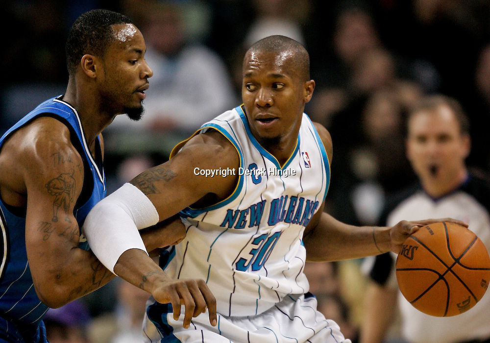 Feb 26, 2010; New Orleans, LA, USA; New Orleans Hornets forward David West (30) is defended by Orlando Magic forward Rashard Lewis (9) during the first half at the New Orleans Arena. The Hornets defeated the Magic 100-93. Mandatory Credit: Derick E. Hingle-US PRESSWIRE
