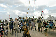 Mundari herdsmen celebrate the slaughtering of a cow at a cattle camp in Central Equatoria Province. The tribe suffered from inter-tribal conflicts and cattle rustling in the northern part of the province forcing them to move further south in search of safer grazing land. Thousands of people have been killed and hundreds of thousands displaced by inter-tribal violence, exacerbated by climate change induced draught and political rivalry.<br /> Kuruki, South Sudan. 12/10/2009.
