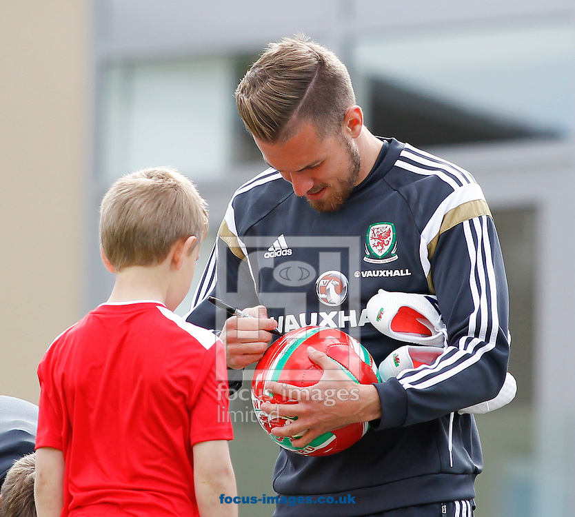 Aaron Ramsey signs a ball for a fan before the Wales Training session at the Vale Resort, Hensol<br /> Picture by Mike Griffiths/Focus Images Ltd +44 7766 223933<br /> 08/06/2015