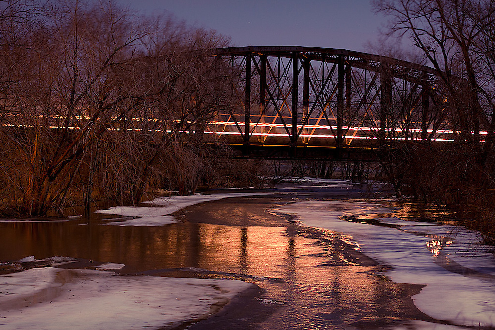 A westbound BNSF intermodal train flies over the flooded Spoon River well after dark on a full moon night on the Illinois prairie.
