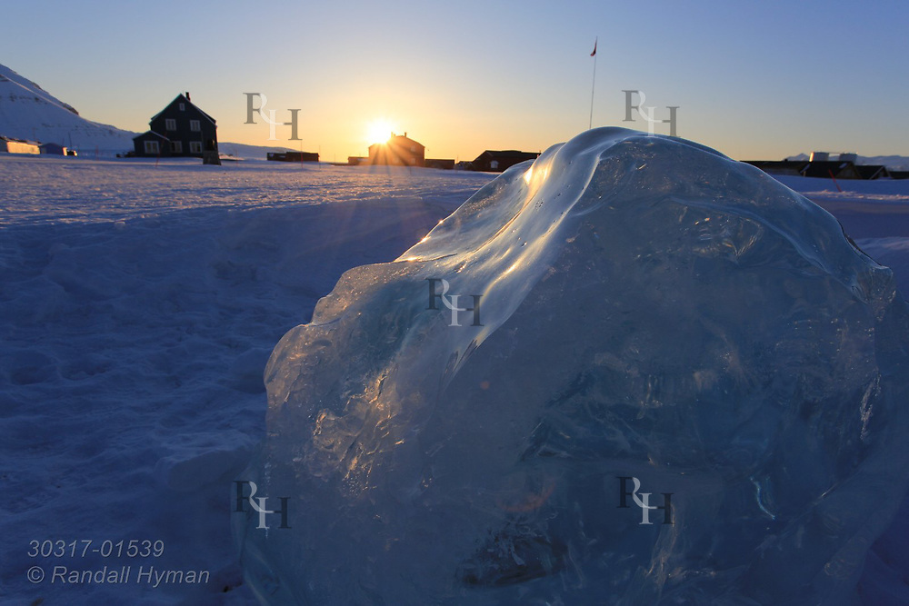 "Block of glacial ice, hauled into village for alcoholic drinks ""on the rocks,"" frames enening sun in April at the international science village of Ny-Alesund on Spitsbergen island in Kongsfjorden; Svalbard, Norway."