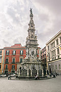 "The Spire or Guglia of the Immaculate Virgin in Naples, southern Italy. The Guglia dell'Immacolata is a monument that stands in the square in front of the church of Gesù Nuovo. It is the tallest and most ornamental of three such ""plague columns"" in Naples."