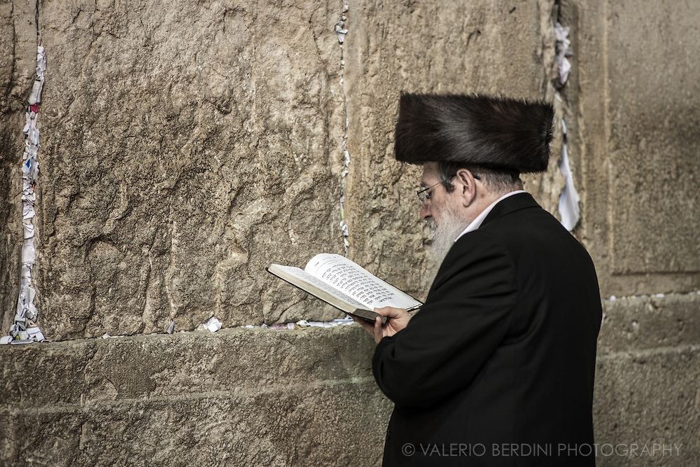 A Haredim reads prayer from a siddur (prayerbook) at the Kotel. He wears a Shabbat Shtreimel, The fur hat worn by married Haredim on Jewish holidays. The piece of papers into the crevices of the wall contain written prayers to God left as wishes by Jewish believers. Over a million notes are placed each year. The notes are collected twice a year and buried on the nearby Mount of Olives.