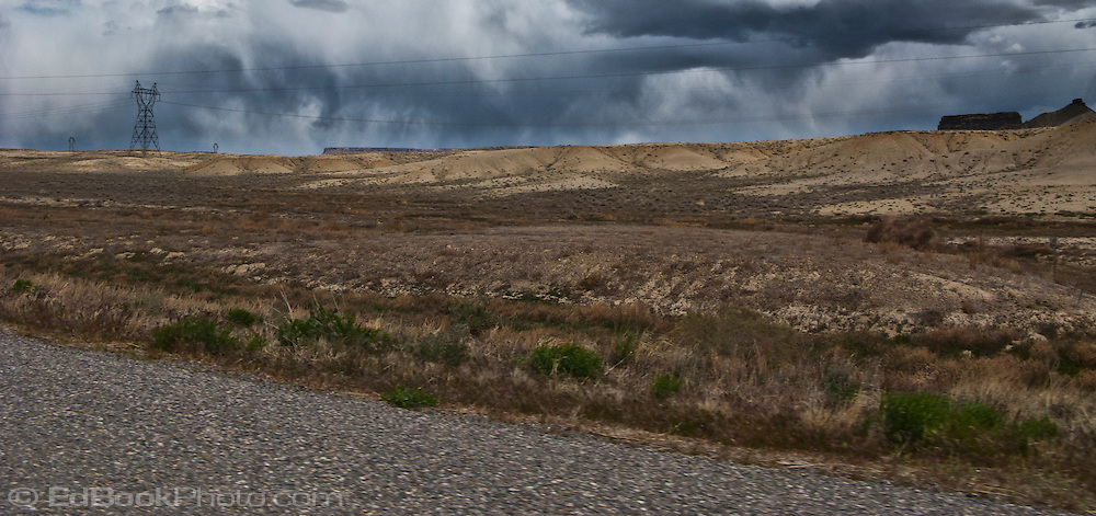 storm clouds drop streams of rain in the distance beyond mesas and power transmission lines along highways US 491/US 160 in northwesten New Mexico near the Colorado state line.  panorama
