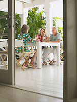 Three people sitting at verandah table