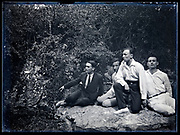 group of four men sitting on a rock in nature setting circa 1930s