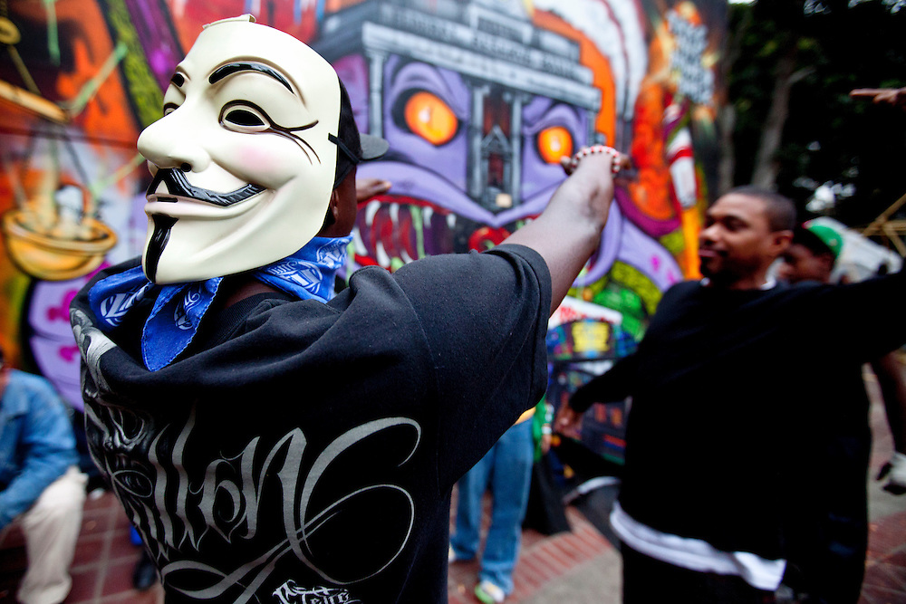 A man wearing a Guy Fawkes mask dances in front of city hall on Saturday, November 12, 2011 in Los Angeles, Calif. (Photo by Gabriel Romero ©2011)