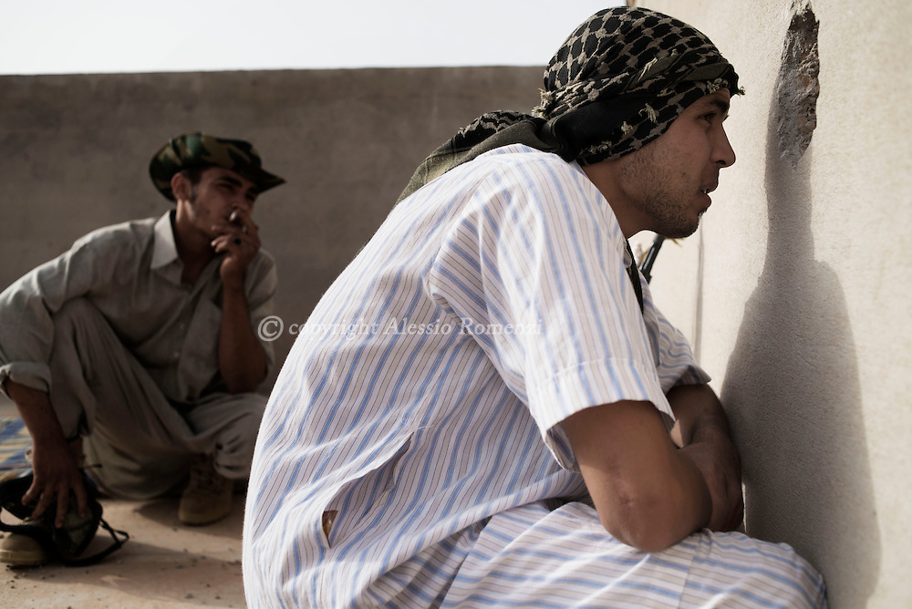 Libya: Libya's Government of National Accord's (GNA) fighters hide on a rooftop in west Sirte to check ISIS movements. Alessio Romenzi