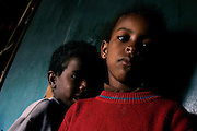 Almas, 5 year-old-girl, and Bilal, 3, her brother, are portrayed while in their house in the unrecognised village of Wadi el Na'am, pop. 4000, close to Beer Sheva, the capital of the Negev, a large deserted area in the south of Israel.  Wadi el Na'am is located near a large industrial site, Ramat Hovav, and has no infrastructure nor electric energy. Water is provided only via storage tanks. It has no health services as the only clinic is deemed illegal and bound to be demolished, as the rest of the structures in the area. Numbering around 200.000 in Israel, the Bedouins constitute the native ethnic group of these areas, they farm, grow wheat, olives and live in complete self sufficiency. Many of them were in these lands long before the Israeli State was created and their traditional lifestyle is now threatened by subtle Governmental policies. The seven Bedouin towns already built are all between the 10 more impoverished towns in Israel.
