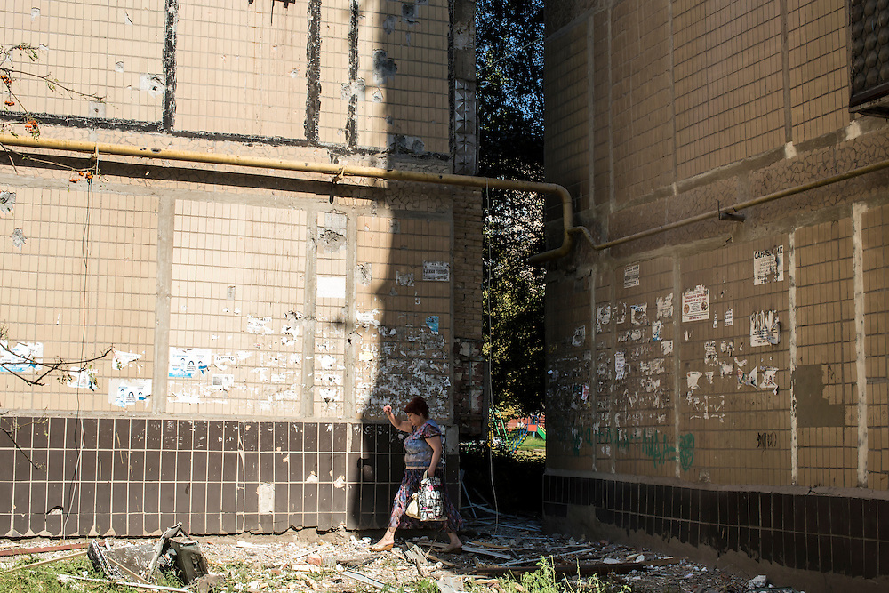 A woman steps over rubble from an apartment building that was hit by a suspected grad rocket strike on Tuesday, July 29, 2014 in Donetsk, Ukraine.
