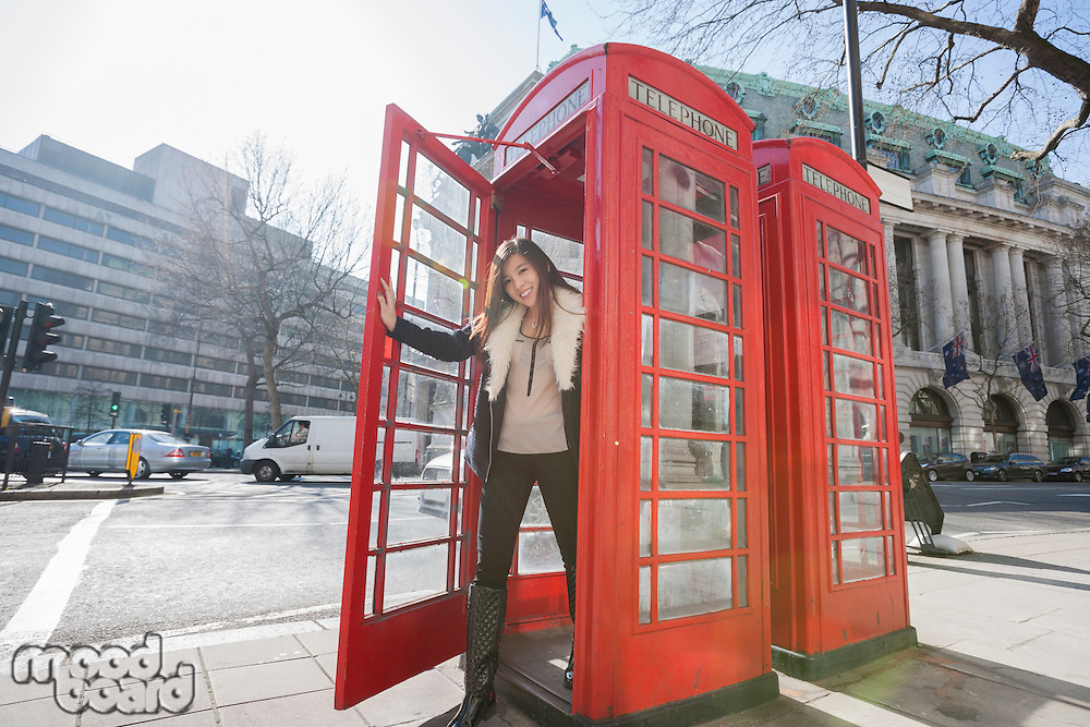 Portrait of happy young woman opening door of telephone booth at London; England; UK