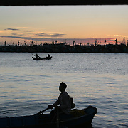 """Boatmen take fishermen to their trawlers at dusk off the coast of Vung Tau, Vietnam, a popular beach resort a few hours' drive from Ho Chi Minh City. Former glam rock star Gary Glitter is currently behind bars in the resort town, facing charges of child molestation. Glitter, whose real name is Paul Gadd, was convicted in Britain in 1999 of possessing child pornography and served two months in jail. In 2002 he was kicked out of Cambodia, a country with lax regulation of prostitution. Glitter's 1970's hit """"Rock and Roll (Part 2)""""  is played regularly at sporting events throughout North America and Europe."""