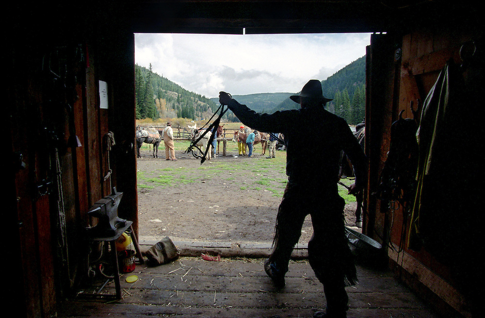 Preparing the horses at the barn for a guided hunt in the Colorado Rocky Mountains