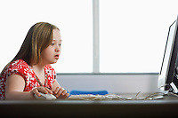 Girl (10-12) with Down syndrome using computer in computer lab