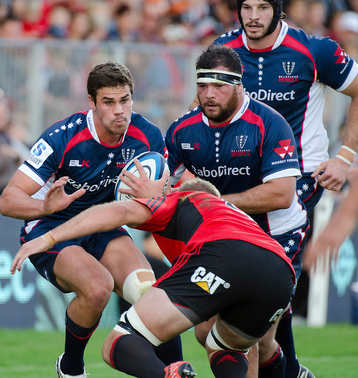 Rebels Tom English, left, fends off Crusaders tackler Luke Whitelock in the Super Rugby match at AMI Stadium, Christchurch, New Zealand, Sunday, April 28, 2013. Credit:SNPA / David Alexander.
