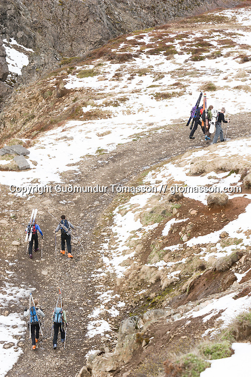 Group of skiers hiking uphill on a road.