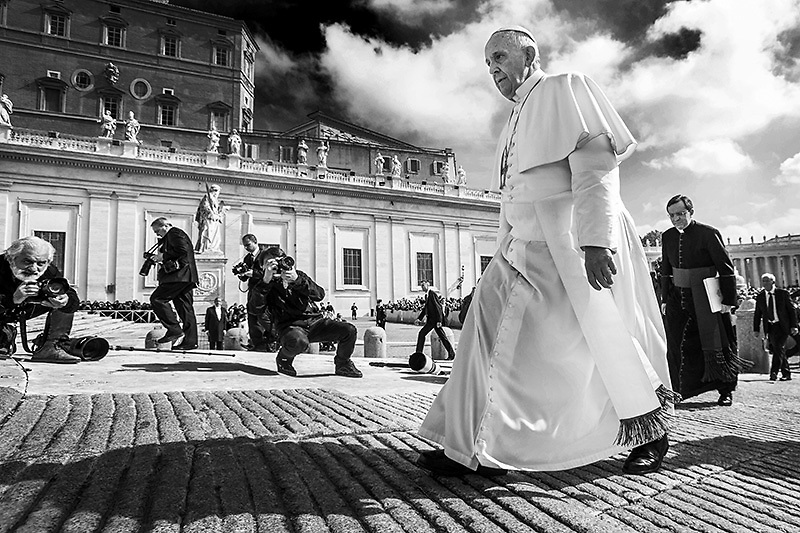 "Pope Francis walks past photographers during his general weekly audience in St. Peter's Square at the Vatican. Pope Francis appealed for equal pay for equal work today, calling compensation disparity a ""pure scandal""."