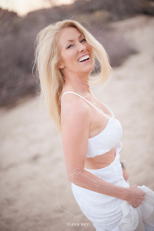 Gorgeous mature woman  in a beautiful white dress smiling in the desert Kim Tang, Bikram yoga teacher in Johsua Tree, CA