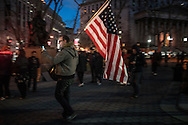 Protester carries an American flag at an Anti-Trump rally in Lower Manhattan, after the Trump administration implemented a ban on entry to citizens of 7 Muslim-majority nations into the United States.  New York, New York, USA.  29 January 2017