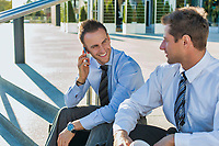 Mature businessman smiling and talking on smartphone while sitting with colleague