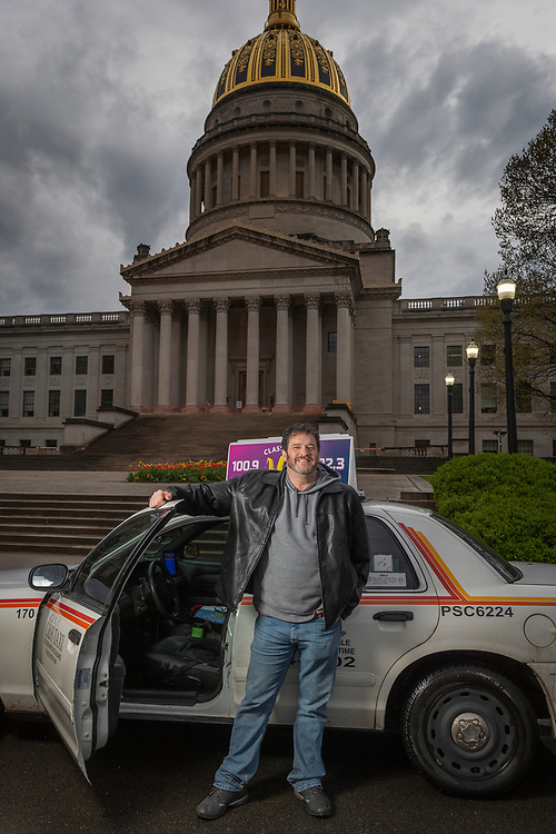 Mike Pushkin (D - Kanawha, 37) poses for a portrait with his taxicab outside of the State Capitol building in Charleston, W.V., on Tuesday, April 24, 2018.