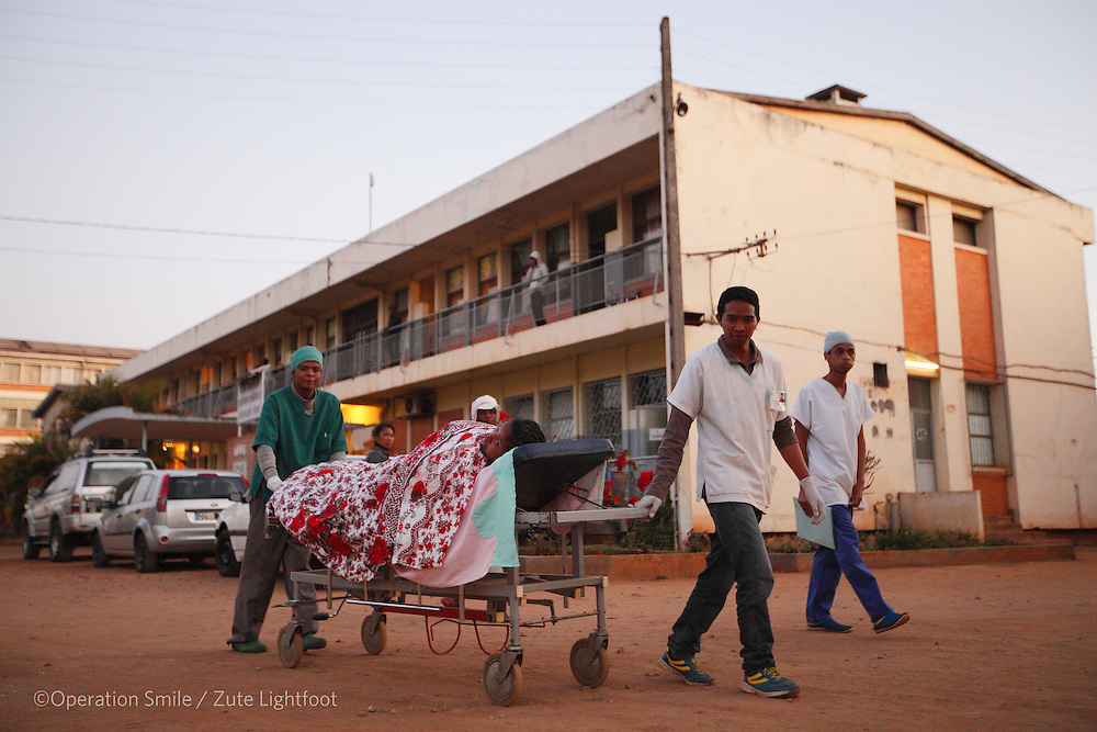Patient being pushed on a trolley across the hospital car park from the operating room to the post ward at Antsirabe Hospital. Antsirabe Clinic Project sponsored by the Swedish Postal Code lottery. Madagascar. September 2015.<br /> (Operation Smile Photographer &ndash; Zute Lightfoot)
