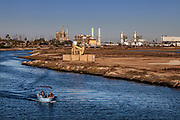 Motorboat in Los Cerritos Wetlands with oil refineries in the distance, Long Beach, california, USA