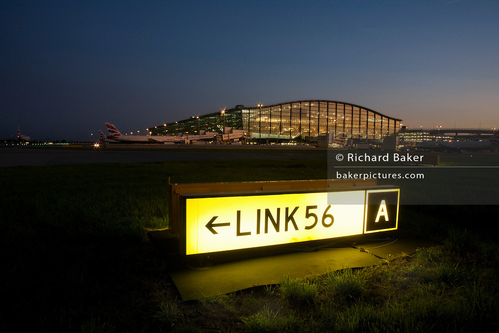An exterior dusk view Terminal 5 building and a taxiway sign for pilots to navigate around complicated Heathrow Airport.