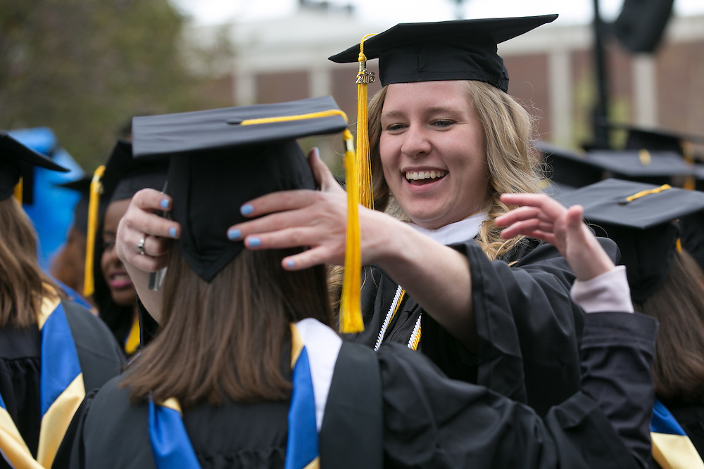 Tara Sullivan of New Marlborough, Massachusetts helps Sarah Vogel of Montclair, New Jersey with her cap at the University of Rochester's Commencement ceremony in Rochester on Sunday, May 15, 2016.