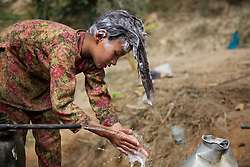 Durga and Niruta&rsquo;s oldest child Sumitra, 10, washes her hair outside the cow shed one afternoon. <br />