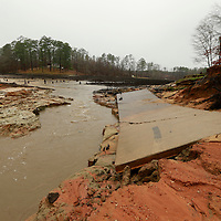 Thomas Wells   BUY AT PHOTOS.DJOURNAL.COM<br /> Water continues to drain past the boat ramp near the levee at Lake Whiteside on Monday following a weekend collapse of the levee at the Nettleton Fox Hunting and Fishing Association.