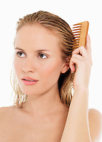 Young Blond Woman Combing wet Hair close up