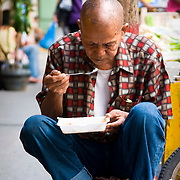 MANILA (Philippines). 2009. An old man eating on the streets of Chinatown in Manila.