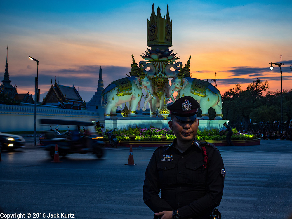 15 OCTOBER 2016 - BANGKOK, THAILAND:  A Thai police officer guards an intersection in front of the Grand Palace in Bangkok during mourning rituals for the late Bhumibol Adulyadej, the King of Thailand. King Bhumibol Adulyadej died Oct. 13, 2016. He was 88. His death comes after a period of failing health. With the king's death, the world's longest-reigning monarch is Queen Elizabeth II, who ascended to the British throne in 1952. Bhumibol Adulyadej, was born in Cambridge, MA, on 5 December 1927. He was the ninth monarch of Thailand from the Chakri Dynasty and is known as Rama IX. He became King on June 9, 1946 and served as King of Thailand for 70 years, 126 days. He was, at the time of his death, the world's longest-serving head of state and the longest-reigning monarch in Thai history.     PHOTO BY JACK KURTZ