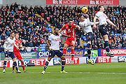 Bolton Wanderers forward Gary Madine  heads the ball away from the waiting MK Dons defender Joe Walsh  during the Sky Bet Championship match between Bolton Wanderers and Milton Keynes Dons at the Macron Stadium, Bolton, England on 23 January 2016. Photo by Simon Davies.