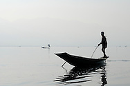Burma/Myanmar, Inle Lake. Fishermen from Inle Lake.<br /> <br /> They're especially famous for their unique way of rowing. Unlike others, Intha fishermen use their legs to row their small boats, so that they have free hands. By balancing on the helm and paddling in a circular motion with one leg they make their boats moving.They also use special tall conical nets to catch fish. Rowing with legs allows them to drop nets over passing fish, which they can spot in the clear and shallow water.