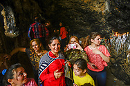 Christian pilgrims inside one of the caves at the Rabban Beya Temple. The 4th century Christian monastery is a series of monastic caves carved into a mountain high above the Shaqlawa valley and an important pilgrimage site for the Assyrian community. Shaqlawa, Iraq. 22/04/2014.