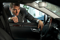 Man looking at new car in showroom