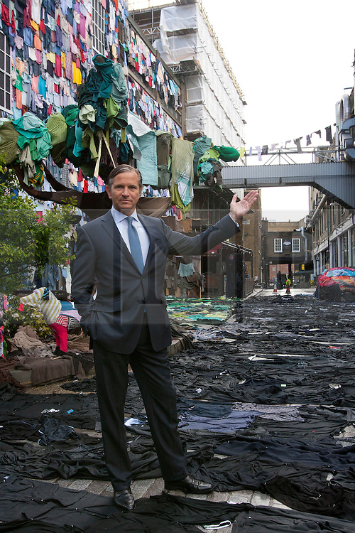 © licensed to London News Pictures. London, UK 26/04/2012. Marc Bolland, CEO of M&S, posing in a street covered with clothes from walls, the road, and the pavement to a fabric-strewn bench, car and even a dog to illustrate future uses for old clothes in Brick Lane. M&S will be accepting people's old and unwanted clothes for their charity campaign with Oxfam. Photo credit: Tolga Akmen/LNP