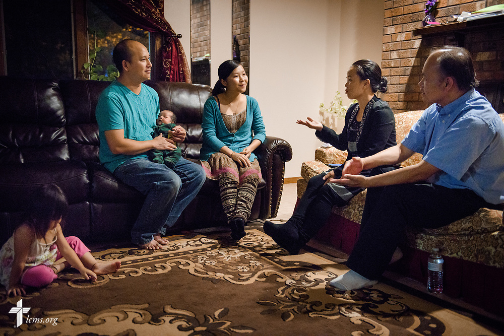 The Rev. Moua Vang (right), associate pastor at Benediction Lutheran Church, Milwaukee, Wis., and his wife Kou, make a home visit with Soua Chang and his wife Chuchee Leeyer on Monday, Aug. 14, 2017, in Milwaukee.  LCMS Communications/Erik M. Lunsford