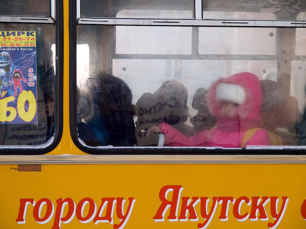 Maedchen hinter einer Autobus Glasscheibe in Jakutsk. Jakutsk hat 236.000 Einwohner (2005) und ist Hauptstadt der Teilrepublik Sacha (auch Jakutien genannt) im Foederationskreis Russisch-Fernost und liegt am Fluss Lena. Jakutsk ist im Winter eine der kaeltesten Grossstaedte weltweit mit durchschnittlichen Winter Temperaturen von -40.9 Grad Celsius. Die Stadt ist nicht weit entfernt von Oimjakon, dem Kaeltepol der bewohnten Gebiete der Erde.<br /> <br /> Girl sitting behind a window of a Yakutsk bus. Yakutsk is a city in the Russian Far East, located about 4 degrees (450 km) below the Arctic Circle. It is the capital of the Sakha (Yakutia) Republic (formerly the Yakut Autonomous Soviet Socialist Republic), Russia and a major port on the Lena River. Yakutsk is one of the coldest cities on earth, with winter temperatures averaging -40.9 degrees Celsius.