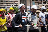 Men supporting the Egyptian president Mohammed Morsi march around a camp with homemade weapons, one year after the election. Cairo, Egypt.
